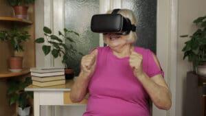 En äldre dam sitter framför ett fönster med VR-glasögon på sig.